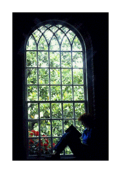 person reading next to a large window